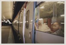 2003-1054-25 Reizigers zitten in een trein. De trein is gestopt op een perron van het Centraal Station. Uit een serie ...