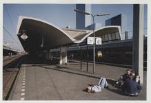 2003-1054-27 Jongeren zitten op perron 6 en 7 van het Centraal Station. Uit een serie van dertig foto's over het ...