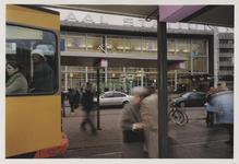2003-1054-29 Ouder echtpaar op het Stationsplein voor de hoofdingang van het Centraal Station. Een tram rijdt voorbij. ...
