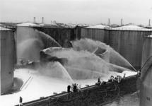 1968-94 Op de voorgrond blust de brandweer een brandende kerosinetank bij Pakhoed (voorheen Pakhuismeesteren) aan de ...