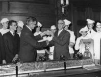 1977-2065 Burgemeester W. Thomassen (links) en wethouder J. Worst (rechts) zijn jarig. De jarigen overhandigen elkaar ...