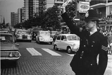 XXXIII-1513 Een Britse politieagent, te gast in Rotterdam, regelt het verkeer in de Karel Doormanstraat.