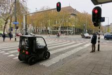 259 De kruising van de Aert van Nesstraat en de Coolsingel. Voor het stoplicht staat een kleine elektrische auto. Op de ...