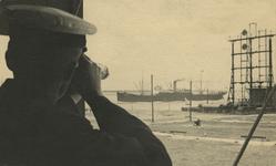 FD-3166 Een man met verrekijker, gericht op een schip op de Nieuwe Waterweg bij Hoek van Holland. Rechts de semafoor, ...