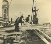 FD-3223 Mannen bezig met de overslag van houten planken in de haven.