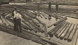 FD-3226 Houtvlotten. Vier houtvlotters begeleiden drijvende boomstammen door de haven of over de rivier.