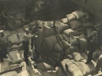 FD-3234 Overladen van balen. Mannen zijn bezig met het laden of lossen van zakken met goederen in het ruim van een schip.