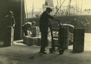 FD-3235 Overladen van kisten. Havenwerkers zijn bezig met het vervoeren van kisten in de haven.