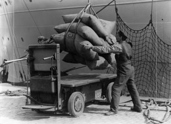 FD-3238 Balen goederen worden vanuit een schip door een havenarbeider op een kar geladen.