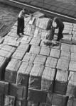 FD-3239 Overladen van pakken in de haven. Twee mannen hijsen goederen in de touwen.