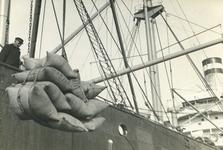 FD-3244 Overladen van balen goederen van de kade naar een schip.