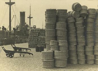 FD-3251 Rijen manden staan opgestapeld op de kade. Op de achtergrond gestapelde kisten. Aan de kade ligt een schip.