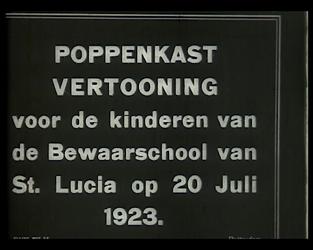 BB-2347 Poppenkast op Lucia Bewaarschool . Een lange stoet vrolijk geklede kinderen verlaat de school om op het ...
