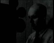 BB-3975 Mogelijk proefopnamen voor een speelfilm. De heer van der Leeuw achter de montagetafel. Geënsceneerde overval ...