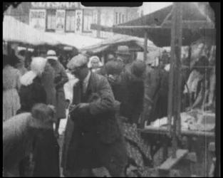 BB-7500 Markt met mensen in verschillende traditionele klederdrachten (o.a. Volendam, Spakenburg). Dorpsomroeper, ...