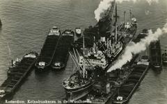 PBK-1987-1224 Waalhaven - Een zeeschip bunkert kolen, aangevoerd door binnenvaartschepen.