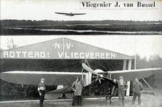 PBK-1987-718 Vliegenier J. van Bussel bij een vliegtuig voor de hangar van de N.V. Rotterdamse Vliegvereniging.