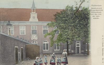 PBK-2286 Weesmeisjes en kinderen op de binnenplaats van het Burgerweeshuis aan de Goudsewagenstraat.
