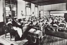 PBK-2292 Weesmeisjes krijgen naailes in een leslokaal, van het Gereformeerd Burgerweeshuis aan de Goudsewagenstraat.