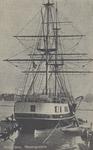 PBK-2725 Schip met masten bij een aanlegsteiger.