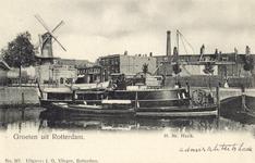 PBK-31-1 Gezicht op het wachtschip Havik aan de Admiraliteitskade. Op de achtergrond molen De Noord en de Oostpoort aan ...