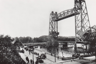 PBK-3614 De verplaatste Koninginnebrug (Brug der Zuchten) en rechts de spoorhefbrug, uit het noorden. Op de achtergrond ...