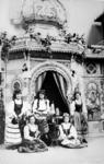1972-1221 Opname in een fotografisch atelier: tentoonstellingsstand met dames in Oost-Europese klederdracht.