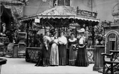 1972-1224 Opname in een fotografisch atelier: tentoonstellingsstand met dames bij een champagnebar.