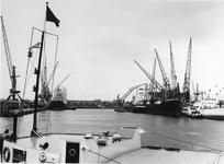 1974-1718 Merwehaven met hijskranen en schepen. Op de achtergrond huizen aan de Schiedamseweg.
