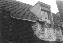1980-1797 Gezicht in de Kalverstraat. Het beschadigd boven gedeelte van een huis met zolderraam.