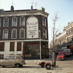 1983-3117 Hoekpand aan de Ketenstraat. Een groot reclamebord op buitenmuur geeft te lezen: E. klop. Uw adres voor ...