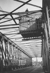 1983-768 Duitse militairen in een hangende controlepost op de Willemsbrug over de Nieuwe Maas.Op de achtergrond de Van ...