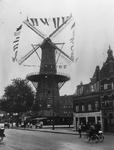 1984-386 Molen De Noord met de wieken versierd op Koninginnedag, op het Oostplein, gezien vanaf de Goudsesingel.