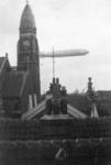 1985-319 Een luchtschip zweeft boven de binnenstad. Links de Koninginnekerk. Op de achtergrond het Wittte Huis.