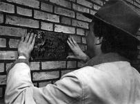 1993-3656 De architect Henk Engel metselt in de gevel van een wonig op de hoek Riederlaan-Hollandsestraat een ...