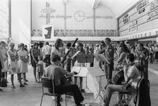 1993-6284 Het Sociaal Muziek Ensemble speelt in de vertrekhal van het Centraal Station.
