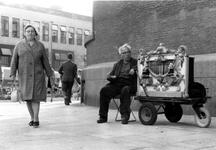 1993-6544 Op de Coolsingel tegen de muur van de Amrobank zit de heer Grinvis met klein orgeltje, op de achtergrond het ...