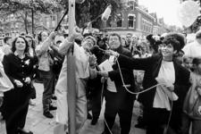 2000-1021 Burgemeester dr. A. Peper hijst tijdens Opzoomerdag in de Opzoomerstraat een vlag, bijgestaan door mevrouw ...