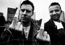2000-1061 Twee jonge mannen demonstreren met een papieren Ku Klux Klan-muts op de middelvinger tegen racisme.