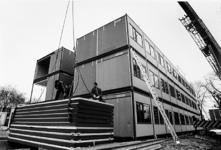 2000-1079 Een groep bouwvakkers is bezig met het opbouwen van complex wisselwoningen, waarschijnlijk voor Hoppesteyn, ...