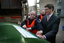 2004-1311 Een medewerker van de ROTEB en wethouder L.L.M. Bolsius bij de speciale afvalcontainer van zorginstelling Den ...