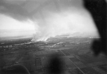 2005-1091 Luchtopname van Rotterdam (genomen vanuit een Duits vliegtuig) in de meidagen van 1940. Rookwolken stijgen op ...