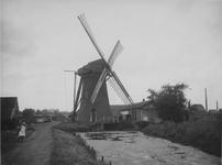 XVI-34-2 De watermolen in de Nieuw Mathenessepolder (gemeente Schiedam). Op de achtergrond links de daken van de ...