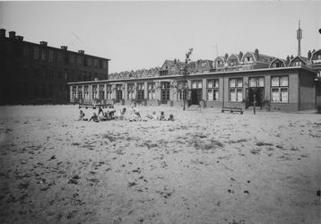 XXII-123-1 Een groepje kinderen speelt op de speelplaats achter de bewaarschool aan de Albregt Engelmanstraat.