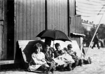 XXXIV-28-13 Een groep kinderen achter de poffertjeskraam bij de Veemarkt en Veemarktstraat, tijdens de Rotterdamse Kermis.
