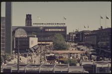 401 Zicht op het Beursplein met winkelpanden van Vroom & Dreesmann, C&A en de Hema. Op het plein staan paviljoentjes en ...