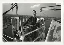 1996-2306 Een man in een tijdelijke buitenlift aan de pyloon van de Erasmusbrug in aanbouw. Op de achtergrond is het ...