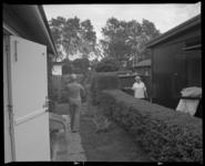 2005-2315-238 Twee bewoners van vakantiewoningen van het Recreatieoord Hoek van Holland met elkaar in gesprek over de heg.