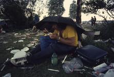2006-47-004 Diareportage van het Holland Popfestival in het Kralingse Bos (4): een jongeman eet onder een paraplu een ...