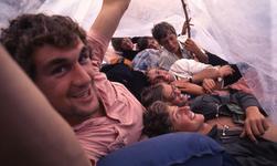 2006-47-029 Diareportage van het Holland Popfestival in het Kralingse Bos (29): jongeren die schuilen onder een plastic zeil.